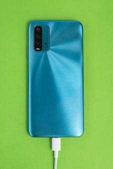 Blauwe mobiele telefoon aangesloten op usb-kabel type c - opladen