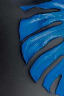 Blauwe monstera deliciosa. helder monsterablad op een abstracte achtergrond. tropische bladmuur