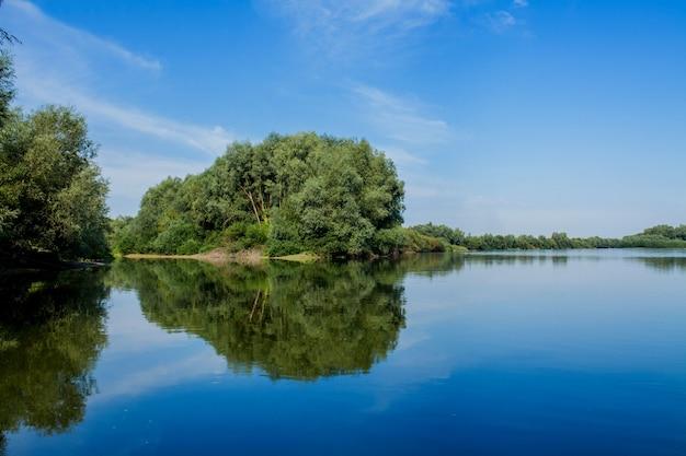 Blauwe mooie hemel tegen de rivier. wolken worden weergegeven in kalm water. aan de horizon, de groene oever van de dnjestr, plaats om te vissen
