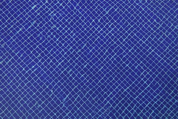 Blauwe mozaïektegels op de bodem van transparant zwembad