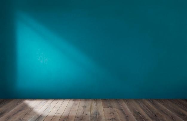 Blauwe muur in een lege ruimte met houten vloer