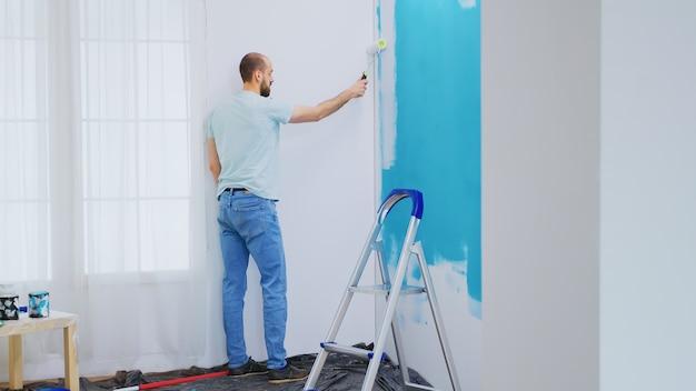 Blauwe muur schilderen met witte verf met rolborstel tijdens huisrenovatie. klusjesman aan het renoveren. appartement herinrichting en woningbouw tijdens renovatie en verbetering. reparatie en decoreren.