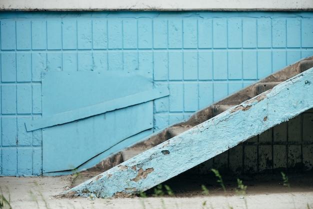 Blauwe muur van gebouw met luik en trap close-up