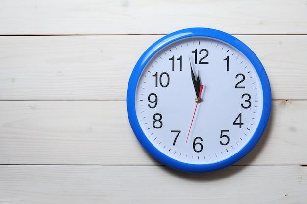 Blauwe muurklok met middernachttijd op houten muur