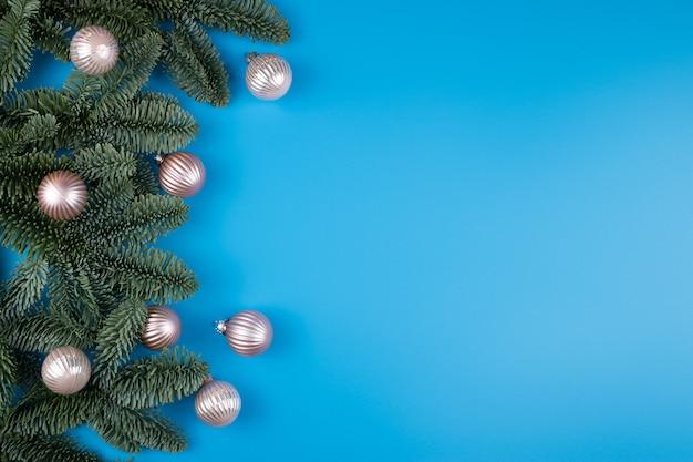 Blauwe nieuwjaar of kerstmis achtergrond met pijnboomtakken en ballen