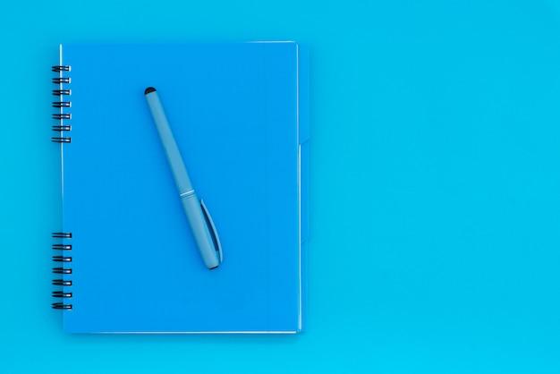 Blauwe notebook met een potlood op een blauwe achtergrond. plat lag sjabloon. plaats voor tekst