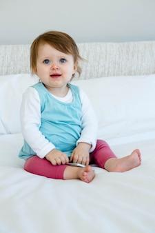 Blauwe ogen baby glimlachen, zittend op het bed