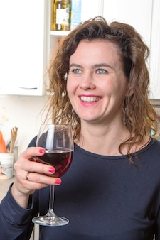 Blauwe ogenvrouw die een glas wijn drinkt