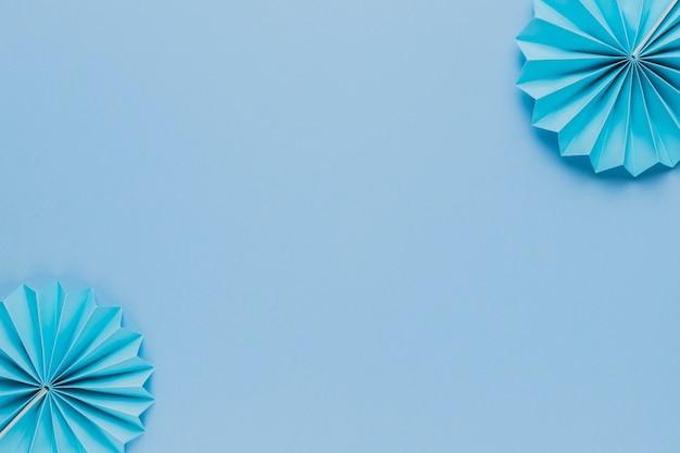 Blauwe origamidocument ventilator bij de hoek van blauwe achtergrond