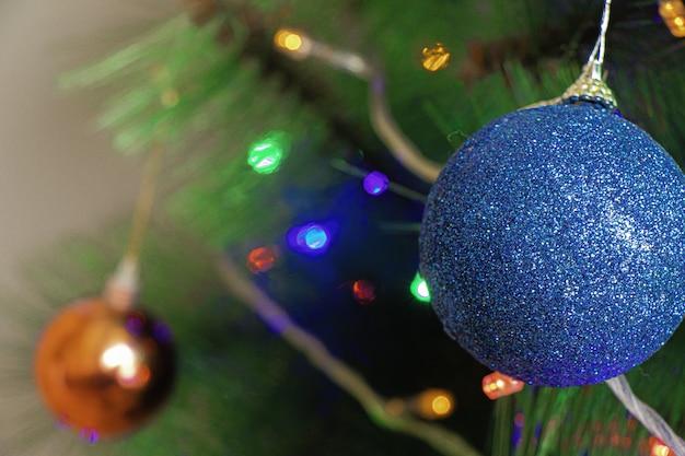 Blauwe ornamentdecoratie op de kerstboom onder de lichten