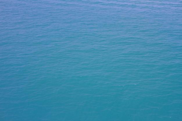 Blauwe overzeese golven oppervlakte zachte en duidelijke hemelachtergrond
