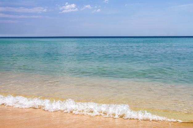 Blauwe overzeese hemel en golven zachte oppervlakte van blauwe oceaan op de dag van de zandige strandzomer, phuket, thailand