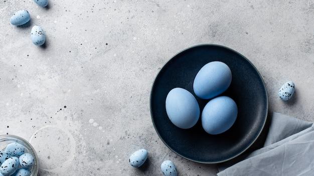 Blauwe paaseieren in een donker blauwe plaat op een grijze betonnen achtergrond. monochroom. banner. plat lag