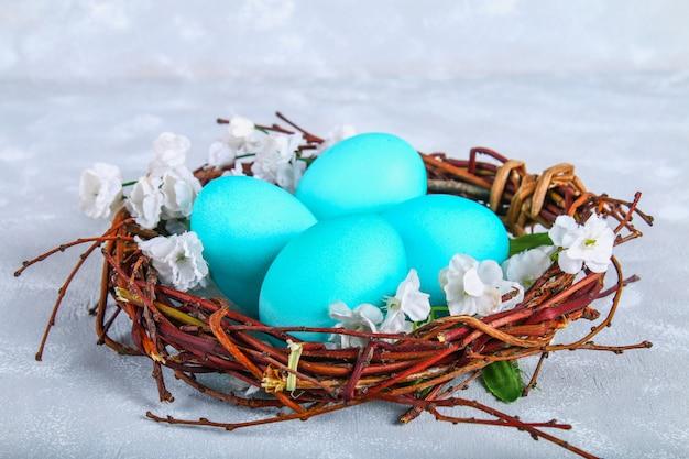 Blauwe paaseieren in een nest met witte bloemen op een grijze concrete achtergrond.
