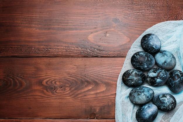 Blauwe paaseieren op de stof op houten planken