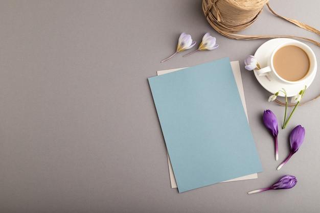Blauwe papieren mockup met lentekrokus en galanthus bloemen en kopje koffie