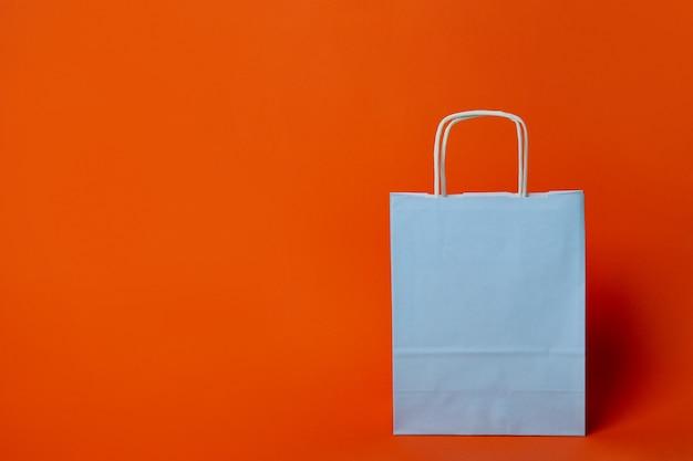 Blauwe papieren zak op oranje achtergrond, ruimte voor tekst