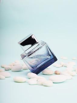 Blauwe parfumfles, eau de toilette lotion omringd door stenen, designer mockup
