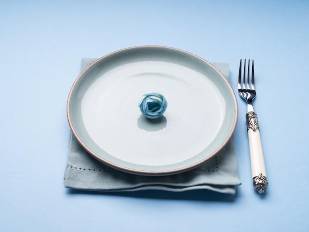 Blauwe pastelkleur ceramische schotel op servet met vork