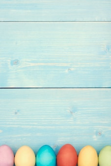 Blauwe pastelkleurplank en kleurrijke paaseieren
