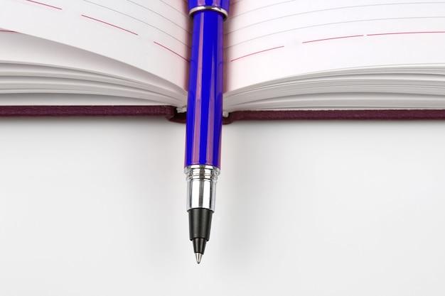 Blauwe pen die op een open notitieboekje ligt
