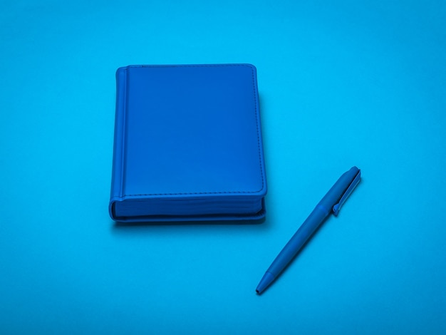 Blauwe pen en blauwe blocnote op een blauwe ondergrond. zwart-wit afbeelding van kantooraccessoires.