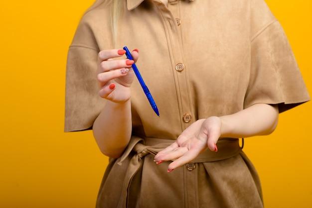 Blauwe pen in vrouwenhand die op geel wordt geïsoleerd.