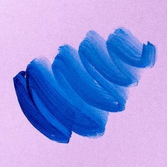 Blauwe penseelstreek op roze achtergrond