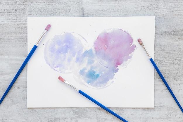 Blauwe penselen en verfvlekken