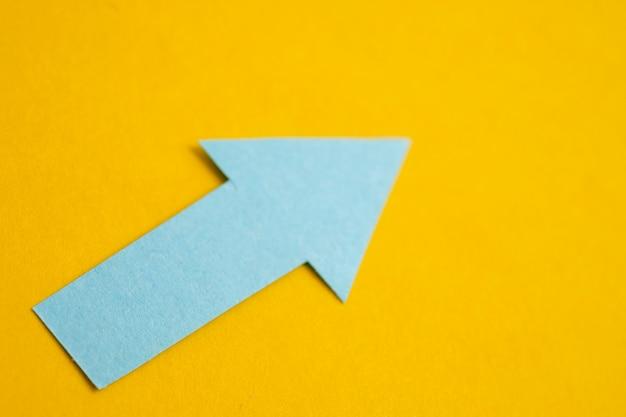 Blauwe pijl gemaakt van papier op een gele achtergrond.