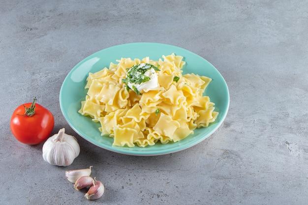 Blauwe plaat van gekookte heerlijke pasta op stenen achtergrond.