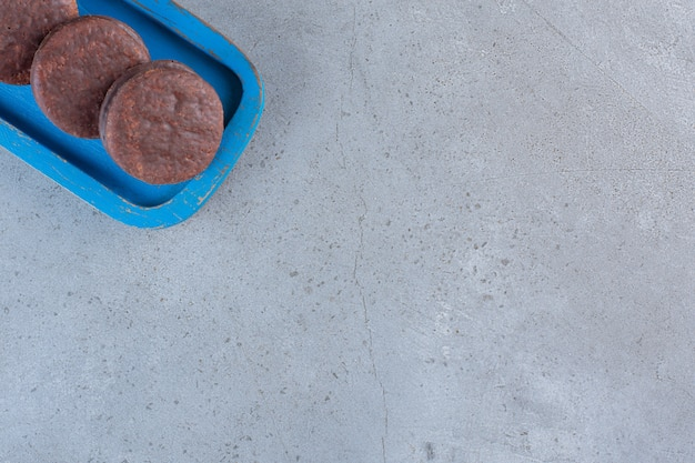 Blauwe plaat van smakelijke chocoladekoekjes op stenen tafel.