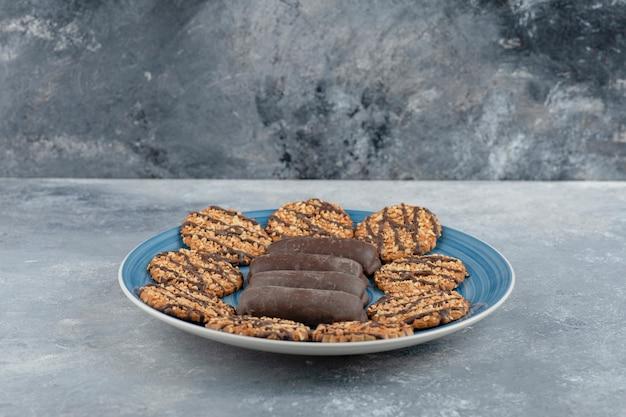 Blauwe plaat vol chocoladetaart en volkoren koekjes op marmeren oppervlak.