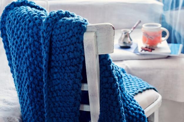 Blauwe plaid op een stoel en koffie met cezve