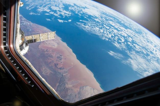 Blauwe planeet aarde uitzicht vanuit raam ruimtestation.