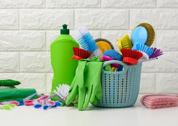 Blauwe plastic mand met borstels, ontsmettingsmiddel in een fles, rubberen handschoenen op de achtergrond van een witte bakstenen muur. huis schoonmaak artikelen set