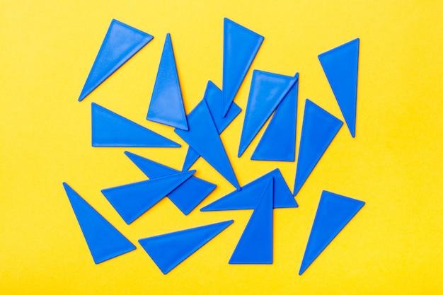 Blauwe plastic platte driehoeken zijn chaotisch verspreid op een gele achtergrond