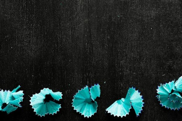 Blauwe potloodspaanders op zwart bureau