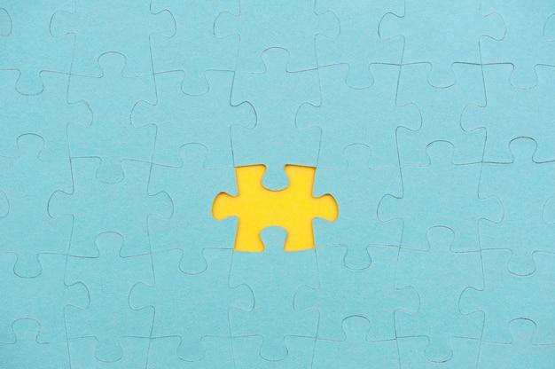 Blauwe puzzelachtergrond met ontbrekend stuk op geel