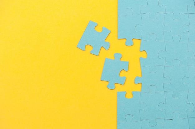 Blauwe puzzelachtergrond met ontbrekend stuk op gele achtergrond bovenaanzicht