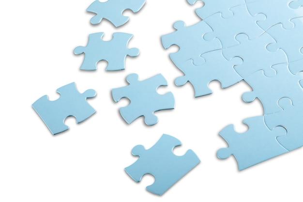 Blauwe puzzelstukjes op grijze achtergrond