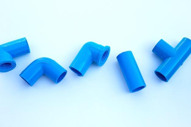 Blauwe pvc-pijpverbinding die op witte muur wordt geïsoleerd.
