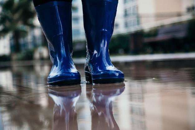 Blauwe regenlaarzen in de plas