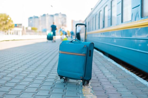 Blauwe reisbagage op treinstation in de buurt van treinreisconcept