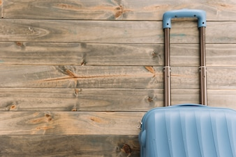 Blauwe reiskoffer tegen houten achtergrond