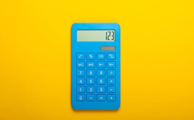 Blauwe rekenmachine op een gele achtergrond. berekenen of tellen. minimalisme. bovenaanzicht