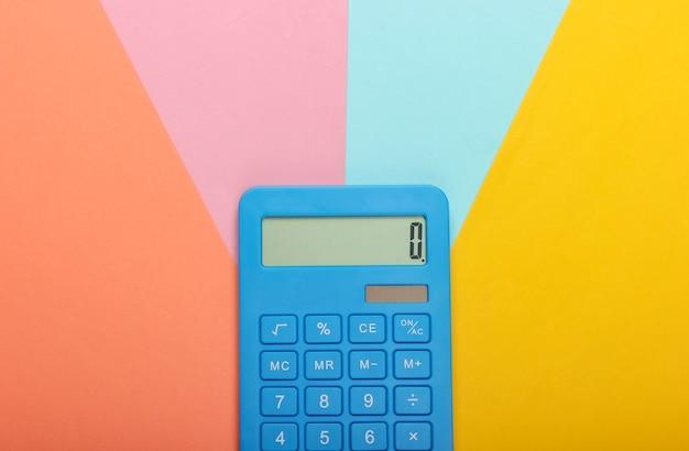 Blauwe rekenmachine op gekleurde pastel achtergrond. berekenen of tellen. minimalisme. bovenaanzicht