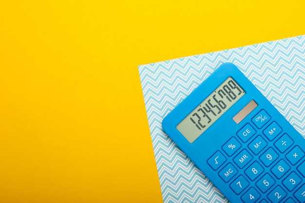 Blauwe rekenmachine op gele blauwe pastel achtergrond. berekenen of tellen. minimalisme. bovenaanzicht