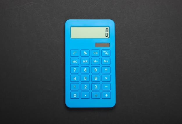 Blauwe rekenmachine op zwarte achtergrond. berekenen of tellen. minimalisme. bovenaanzicht