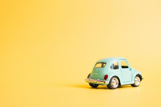 Blauwe retro speelgoedauto op geel. zomer reizen concept. taxi